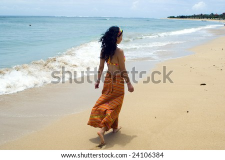 Indonesia, Bali Island, beautiful beach and Indian Ocean at Nusa Dua holiday resort. Girl walking along the beach.