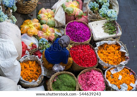 Indonesia, Bali. Pasar Kumbasari outdoor Bali flower market.  Flowers are used daily by Balinese Hindus as symbolic offerings at temples and placed on hand woven trays made from coconut palm fronds.