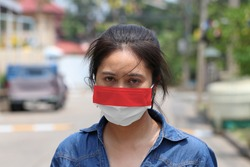 Indonesia flag on hygienic mask. Masked Asian woman prevent germs and wear denim skirt dress. concept of Tiny Particle protection or virus corona or Covid 19.