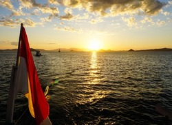 Indonesia national flag on boat captured on sunset from the small island, on Komodo National Park, Flores, Indonesia. Sunset on top of sea wave