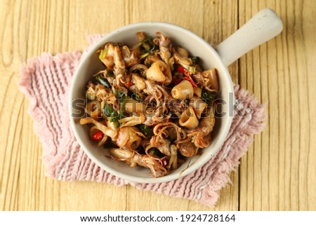 Indonesia traditional cuisine, Oseng cumi asin or stir fry with dried salted  squid. Wooden background  Stock fotó ©