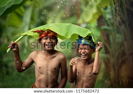 Indonesian Asian children wear traditional headdresses and sarongs, playing rain water and using banana leaves with fun.