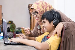 Indonesian boy sitting infront of laptop learning from home with his mother