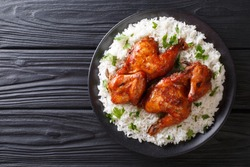 Indonesian chicken baked in ginger garlic sauce served with rice on a plate in close-up. horizontal top view from above