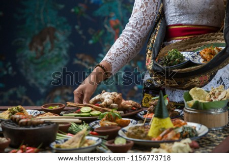 Indonesian cuisine - Many traditional Balinese dishes on the table. Waitress is serving food