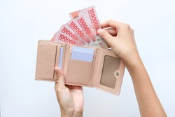 Indonesian hand woman take out showing rupiah money from pink wallet