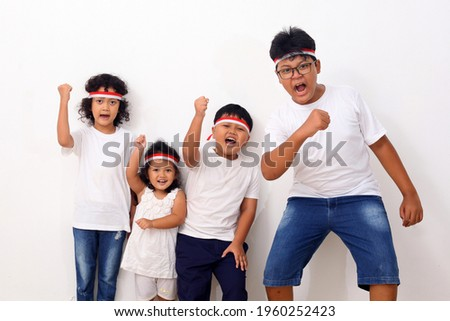Indonesian kids celebrate Indonesia's independence day. They wear red and white ribbons as the symbol of the Indonesian flag. Stock fotó ©