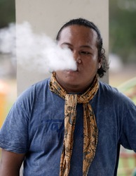 Indonesian man wearing a scarf blowing her cigarette smoke