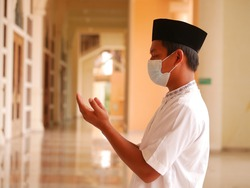 Indonesian muslim young man wearing medical face mask standing while raised hands and praying. Indonesiam moslem man praying with the prayer beads in his hand.
