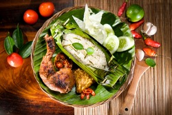 Indonesian Nasi Bakar, Grilled Aromatic Rice wrapped in Banana Leaves served with Spicy Barbeque Chicken, Tempeh and Fresh Salad
