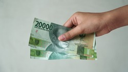 Indonesian rupiah currency, 20,000 rupiah, is held by women's hands