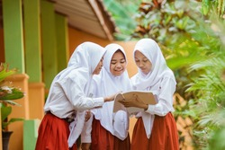 Indonesian school student reading a book together in school garden