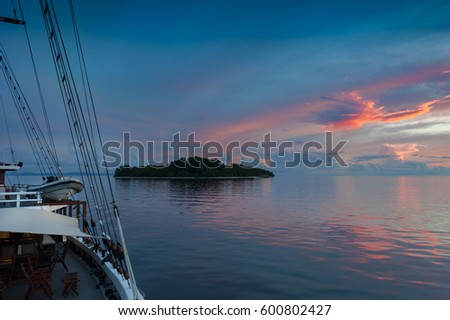 Indonesian Sunset from  a Schooner Sailboat. Sailing through the Raja Ampat archipelago on a traditional phinisi schooner during a glorious sunset.   #600802427