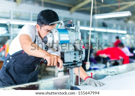 Shutterstock Indonesian worker using a cutter - a large machine for cutting fabrics - in a asian textile factory, he wears a chain glove