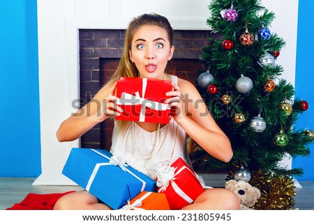 Indoor bright portrait of funny young blonde girl sitting at home near New Year tree and opening Christmas presents. Show tongue and making funny faces.