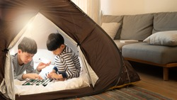Indoor camping tent - Stay at home activity for family during Covid 19 pandemic lockdown concept. Young asian brothers kids playing games together in a teepee in living room. Happy, siblings, april 10