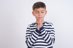 Indoor closeup of Cute Caucasian kid boy wearing knitted sweater against white wall practicing yoga and meditation, holding palms together in namaste, looking calm, relaxed and peaceful.