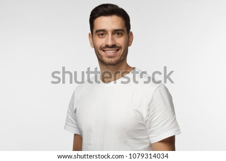 Indoor closeup of young good-looking European man isolated on gray background dressed in white T-shirt showing friendly toothy smile, feeling content, satisfied and confident about work and life