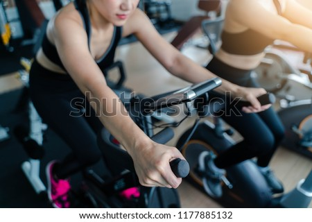 Indoor cycling women doing HIIT cardio workout biking on indoors gym bike #1177885132
