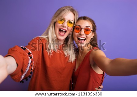 Indoor fashion lifestyle portrait of pretty teen happy friends girls smiling and making selfie over colourful background.