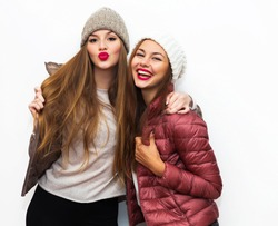 Indoor fashion lifestyle portrait of  two young girl friends standing together and having fun. Looking at camera.Having fun together and sending kisses.