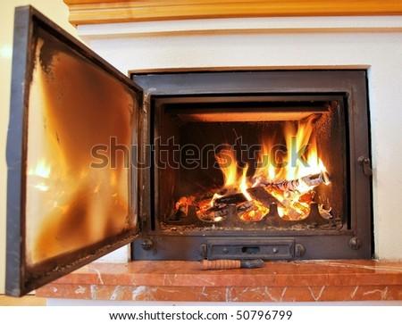 Indoor fireplace with open door.