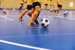 Indoor football training for youth team. Young boys with soccer balls running on wooden parquet. Indoor football soccer school practice. Kids in soccer sportswear