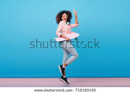 Indoor full-length portrait of confident african girl in pink shirt holding skateboard. Enthusiastic black woman with curly hairstyle posing in studio with blue interior.