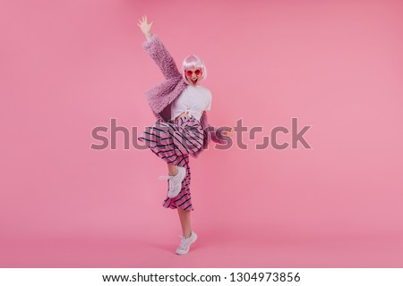 Indoor full-length portrait of pleasant glamorous girl with pink hair. Happy young lady in periwig dancing in white sneakers in studio and laughing.