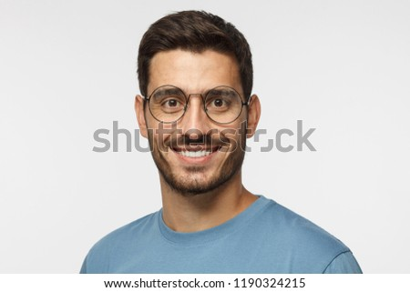 cd0074d96a3 Indoor headshot of young handsome male isolated on gray background dressed  in blue t-shirt