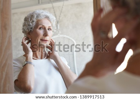 Indoor image of attractive stylish senior mature woman looking in mirror while applying anti-aging cream on her face, getting dressed, going to theatre, adjusting hairstyle. Elegance, age and maturity