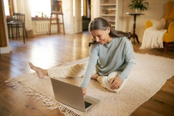 Indoor image of beautiful energetic female on retirement sitting barefoot on floor using laptop turning on calm music for meditation. Elderly European woman surfing internet on portable computer