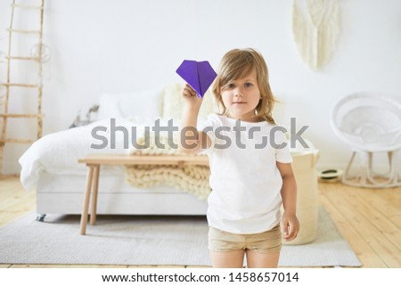 Indoor image of charming little European girl in casual clothes is playing indoors, holding with violet paper plane, going to throw it at camera. Children, fun, games, activity and leisure time