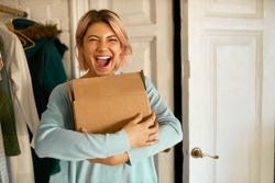 Indoor image of happy cheerful young woman holding cardboard box delivered to her apartment, expressing excitement, going to unpack parcel, having impatient overjoyed look. Food delivery and shopping