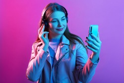 Indoor image of pleasant positive young female taking picture for social networking sites, having headphones, posing isolated over neon background, wearing casual clothes. Technology concept.