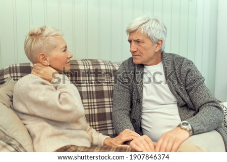 Indoor image of serious senior male with gray hair frowning, sitting on sofa with his unhappy wife, having health problems, suffering from pain in neck. People, age, retirement and health concept Stockfoto ©