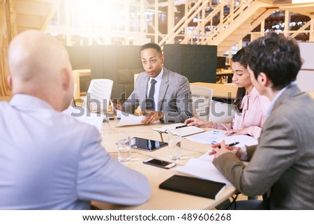 Indoor meeting between 4 business executives in a warm creative environment, making use of tech and documents during the early hours of the morning in preparation for the coming week. #489606268