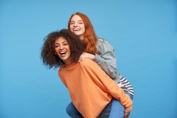 Indoor photo of happy young beautiful ladies rejoicing and smiling widely while looking at camera, being in high spirit while posing over blue background