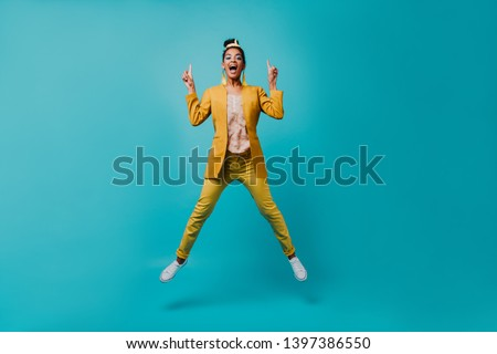 Indoor photo of lovable african girl jumping on blue background. Lovely slim lady in yellow pants funny dancing.