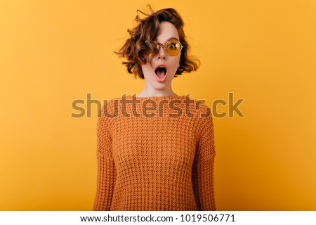 Indoor photo of romantic shocked woman in trendy sunglasses standing near yellow wall. Portrait of dreamy white girl with wavy hair expressing amazement. #1019506771