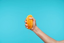 Indoor photo of young attractive hand holding orange and clenching a fists while queezing juice, preparing breakfast while posing over blue background