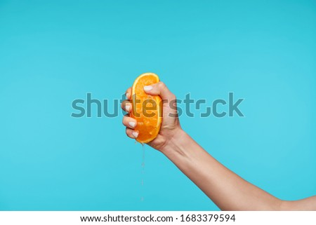 Indoor photo of young attractive hand holding orange and clenching a fists while queezing juice, preparing breakfast while posing over blue background Stockfoto ©