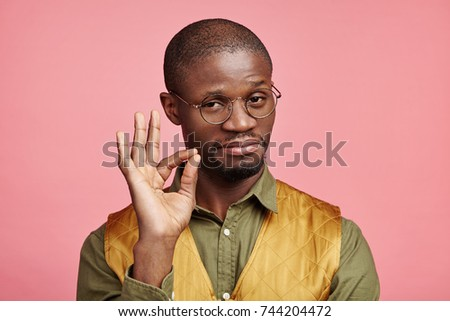 Indoor picture of confident serious male with dark pure skin makes ok gesture, being satisfied with everything, hasn`t any rejections. Satisfied Afro American man isolated over pink background