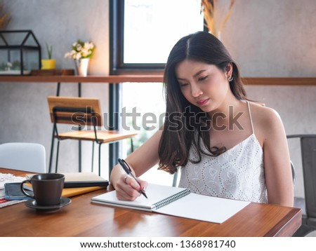 indoor picture of smiling Asia woman writing with notebook #1368981740