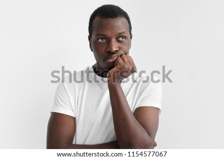 Indoor picture of young African American guy pictured isolated on gray background pressing fist to chin, feeling boring, tired or exhausted, not willing to act in result of stress