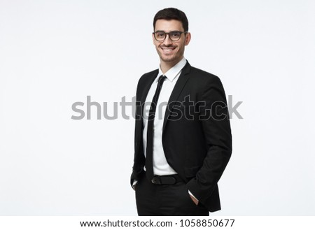 Indoor picture of young business man in glasses pictured isolated on grey background looking straight at camera, showing confidence and providing stability for employees