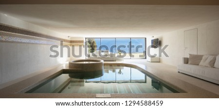 Indoor pool of private villa with lake view and bar area. Nobody inside #1294588459