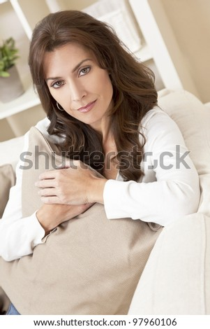 Indoor portrait of a beautiful young brunette woman in her thirties or forties holding a cushion and looking thoughtful