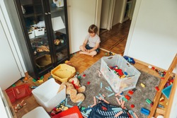 Indoor portrait of a child playing in a very messy room, throwing teddy bear on the floor