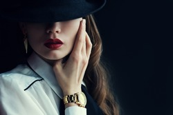 Indoor portrait of a young beautiful  fashionable woman wearing stylish accessories. Hidden eyes with hat. Female fashion, beauty and advertisement concept. Close up. Copy space for text